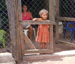 Young girl watches people pass her home